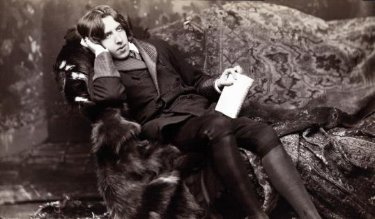 Oscar Wilde Posing on Chair Holding Book
