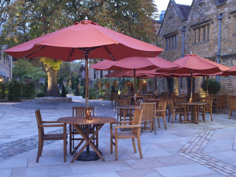 The Lygon Arms Courtyard Dining Tables Red Parasoles