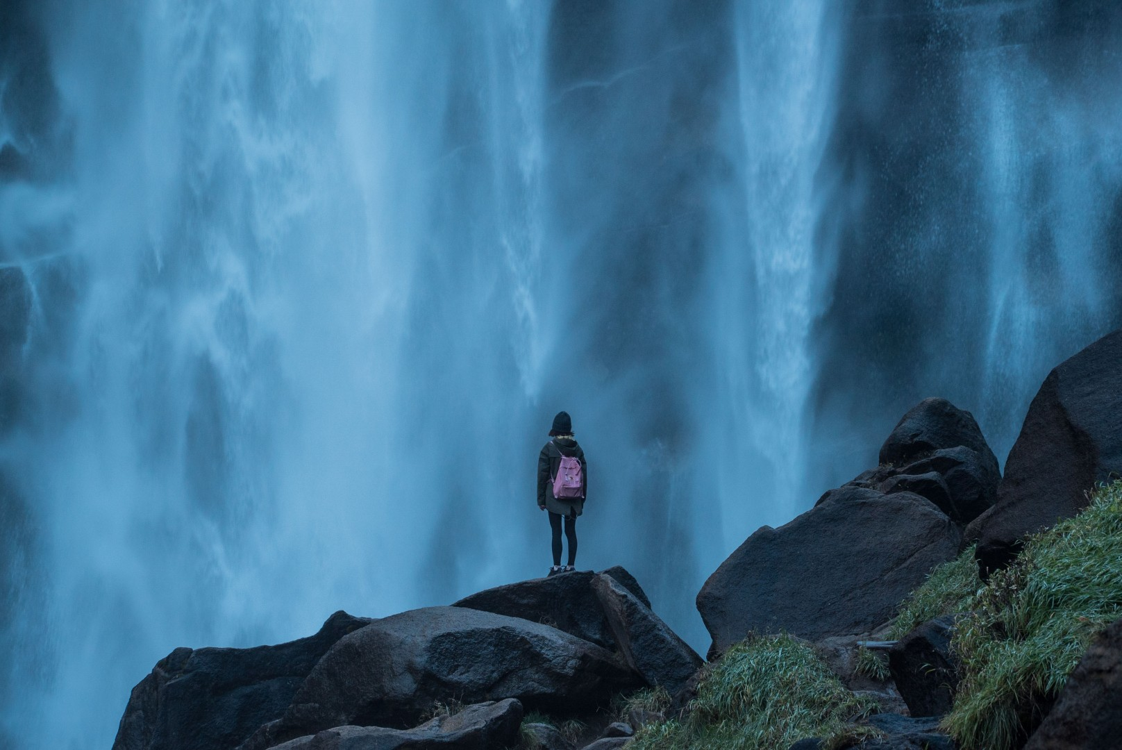 Woman Alone Stood on Rocks Looking At Waterfall